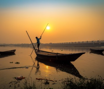 Wooden boat with oarsman at sunset on river Damodar, Durgapur Barrage, West Bengal, India