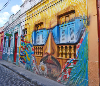 A wall painting of a man's head with moustache and sunglasses, in Recife