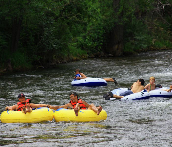 People inner tubing down Clear Creek to cool off from the summer heat in Golden
