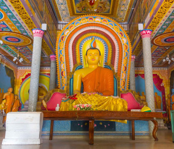 Large statue of Buddha in Bandarawela Buddhist Temple on Sri Lanka with colorful patterns on the wall behind him