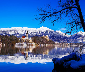 Winter landscape Bled Lake. Bled Lake one of most amazing tourist attractions. View on Island with Catholic Church in Bled Lake with Castle and snowy Alps in Background.