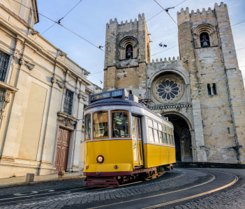 A famous yellow tram 28 passing in front of Santa Maria cathedral in Lisbon Portugal
