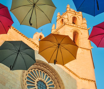 Colorful umbrellas against gothic cathedral of San Pedro in Reus Spain