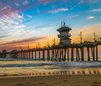 Incredible colors of sunset by Huntington Beach Pier, in the famous surf city in California, USA