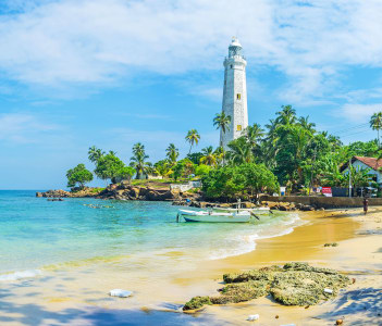 The coastline of the Dondra Cape with the sandy beach and the old lighthouse surrounded by palm garden in Matara