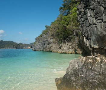 Scenic Rocky Coast and Turquoise Waters on Sunny Day with Clear Blue Sky Caramoan Philippines