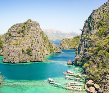 Blue lagoon with longtail boats by Karangan Lake in Coron Palawan