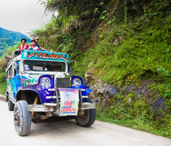 Local public transport jeepney driving fast along a mountain road in province Banaue, Batad, Philippines