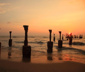 Silhouettes of sea piers during the sunset in Calicut, India