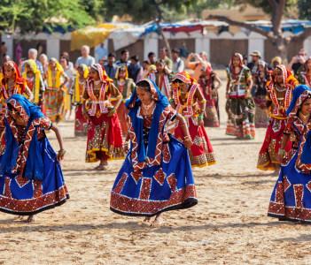 Rajasthani girls in traditional outfits dancing at annual camel fair Pushkar Mela in Pushkar, Rajasthan