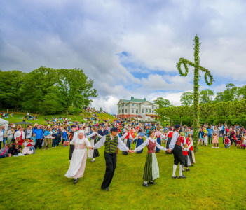Dancers in traditional swedish dress dancing around the maypole for Midsummer celebration in Gunnebo Castle