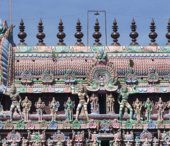The Kumbam the apex on top of the Kumbeswarar temple Gopuram shows a row of pastel colored statues. The bigger images are Dwarapalakas gate keepers.