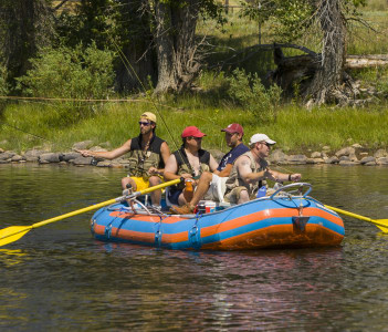 Young men fly fishing from raft on the Big Hole River in Wise River USA