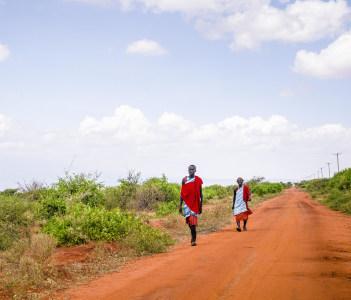 Two maasai men in traditional clothes walking on red african ground, Taveta, Kenya