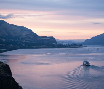 A small cruise boat approaches a group of fishing boats at Columbia River at dawn in USA