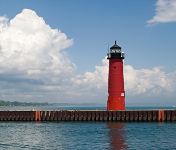 Red lighthouse under dramatic blue and white sky, Lake Michigan in Kenosha, Wisconsin, USA