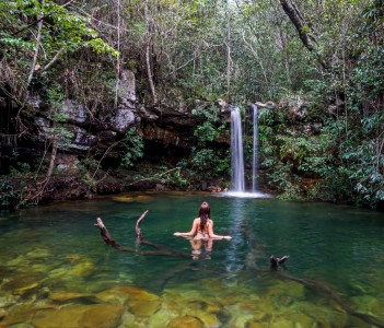 Woman standing in a fallen tree in Loquinhas Waterfall in Chapada dos Veadeiros