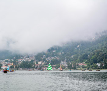 A beautiful landscape of Naini Lake & tourists enjoying boat ride in foggy weather in Nainital, India