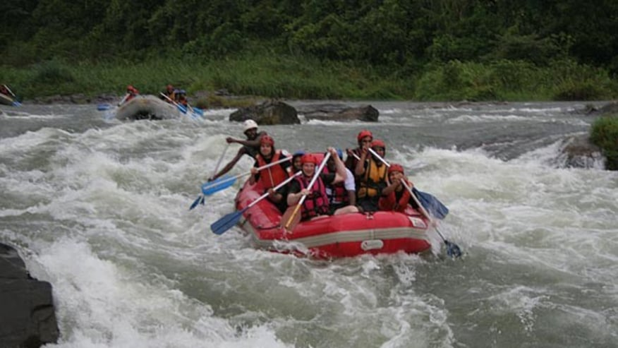Tourists enjoying river rafting