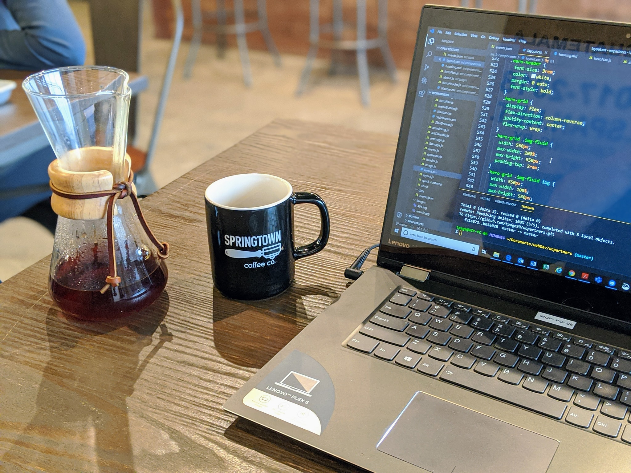 coffee mug with springtown coffee logo next to a small chemex and laptop open with code on screen