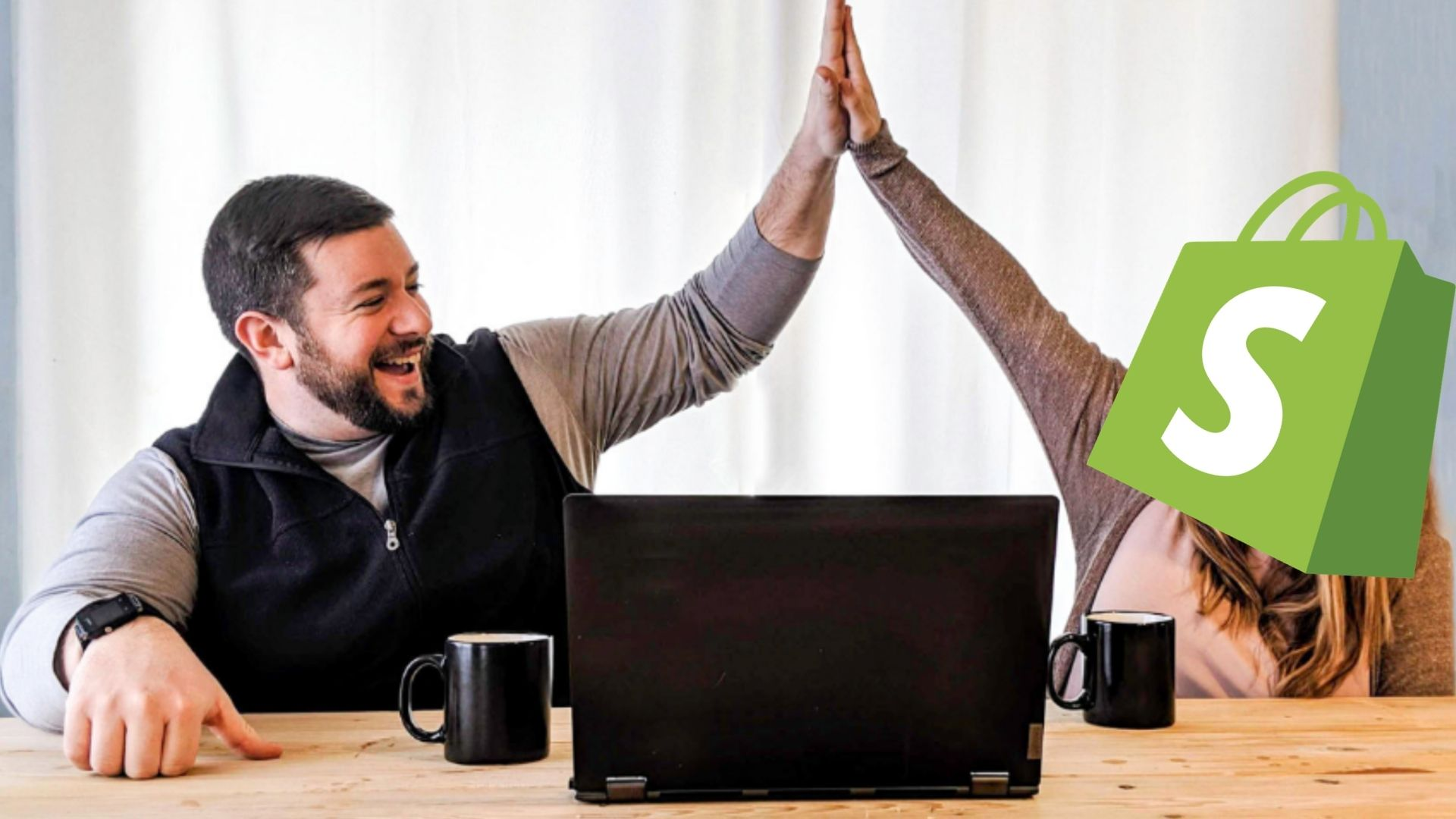 man hi-fiving another person with shopify logo over their face in front of a laptop computer