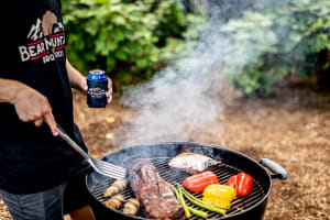 photo of man grilling meat and vegetables