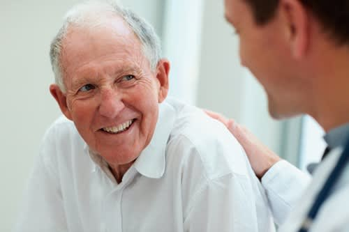 Man smiles as he talks with his doctor