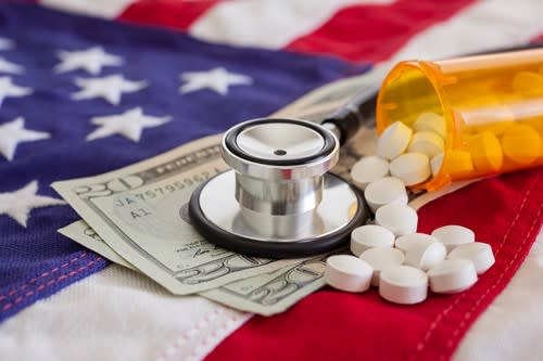 American flag with money and medicine and a stethoscope