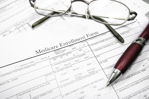 medicare enrollment form with glasses and a pen