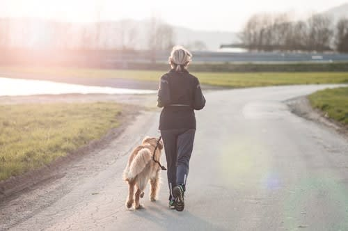 Woman walks outside with her dog