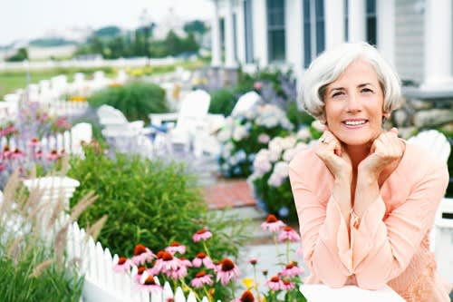 A woman smiles while standing in a garden full of blooming flowers