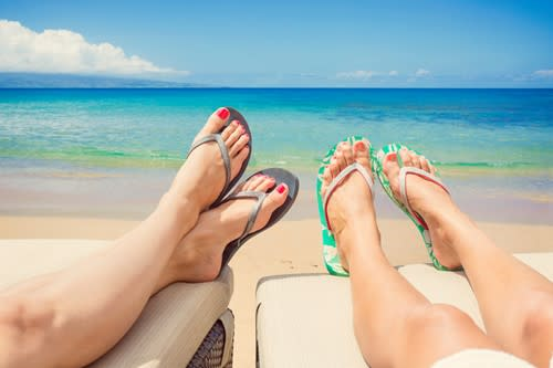 Feet and sandals of two people on the beach