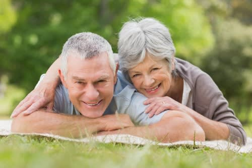 Couple smiling and lying in a park