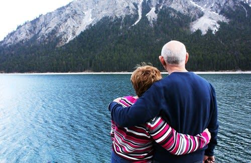 Senior couple looking at lake and mountains
