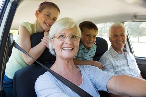 Grandparents in car with their grandchildren