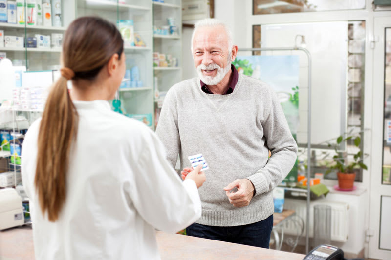 Pharmacist helping senior with prescription