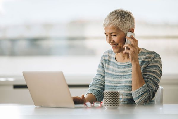Woman on her phone while using her computer
