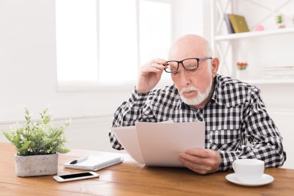 Man sitting at a table reviewing letters