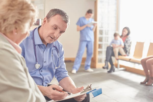 A doctor reviews information with his patient in a lobby