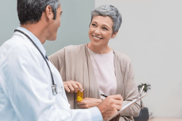 A woman smiles as her doctor gives her a prescription