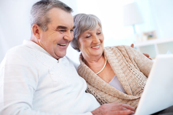 Couple smiles as they use a laptop computer