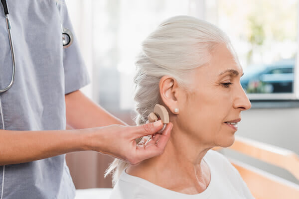 Woman gets a hearing aid from her doctor
