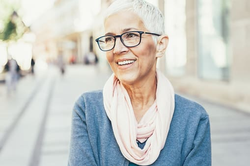 A woman wears fashionable glasses and smiles outside