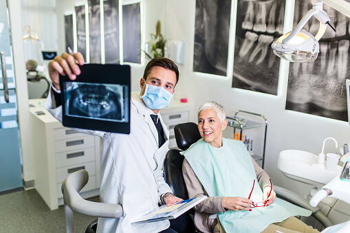 Woman looks at dental xrays with her dentist