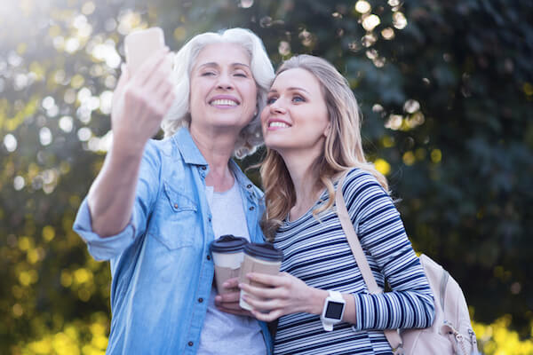 Two women take a selfie picture while holding coffee