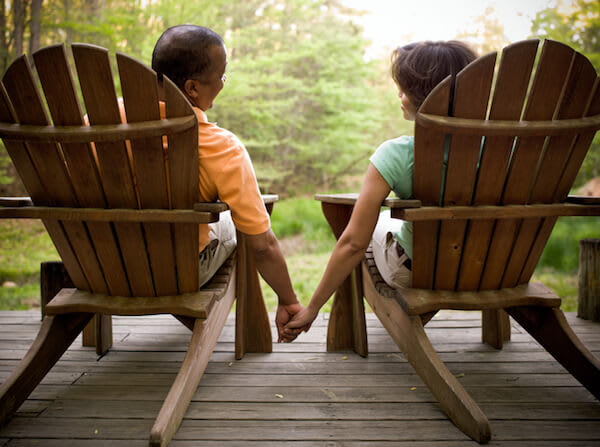 Couple sitting in wooden chairs outside holding hands