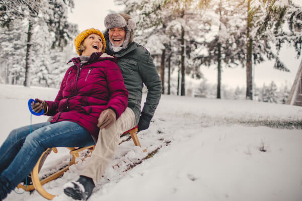 Couple on sled in winter