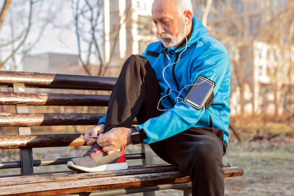 A man ties his shoes on a park bench preparing to exercise