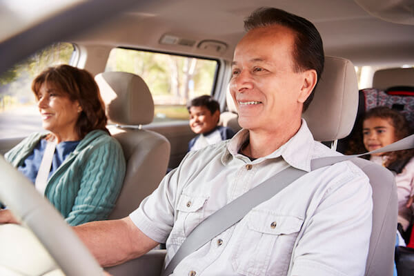 A couple rides in the car with their grandchildren