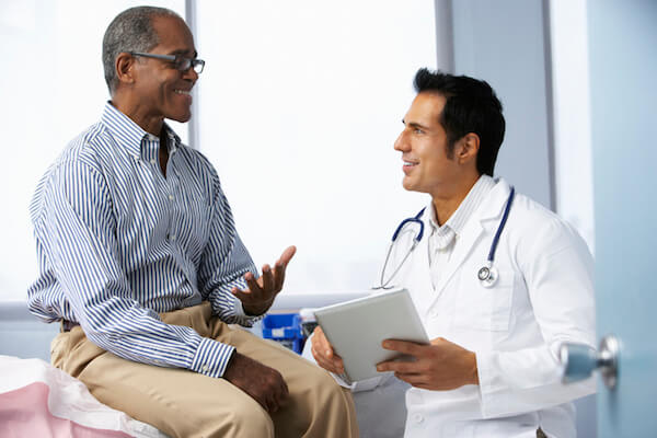 A patient smiles as he speaks with his doctor in the doctors office